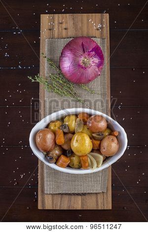 Roasted vegetables dish with potatoes, carrots, mushrooms and onion