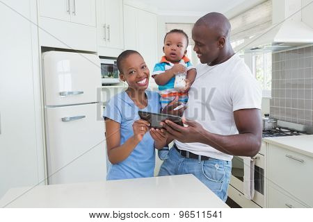 Happy smiling couple with his babyboy using digital tablet in the kitchen