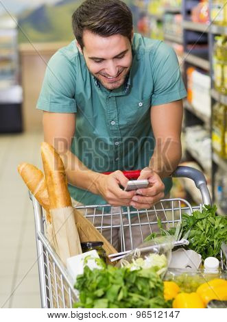 Smiling man buy products and using his smartphone at supermarket