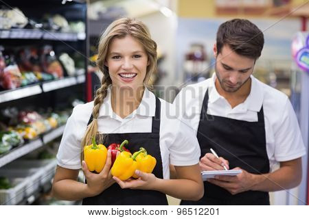 Portrait of smiling blonde woman having vegetables and writing on notepad at supermarket