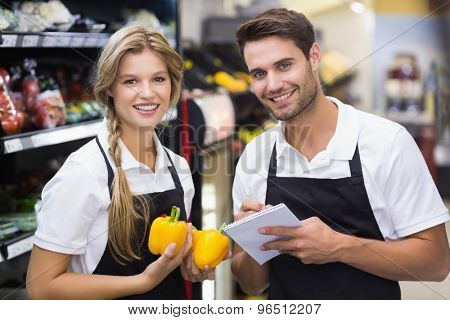 Portrait of two colleagues having a vegetables and writing on notepad at supermarket