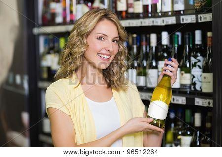 Portrait of a smiling pretty blonde woman showing a wine bottle in supermarket