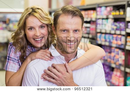 Portrait of smiling casual couple with arm around in supermarket