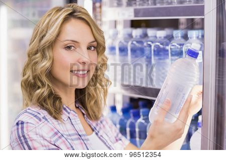 Portrait of a smiling pretty blonde woman taking a water bottle in supermarket