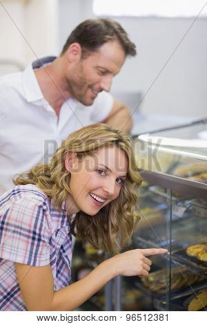 Portrait of a smiling blonde woman looking at pastry in cafeteria