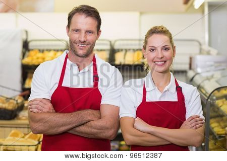 Portrait of smiling bakers with arms crossed in bakery