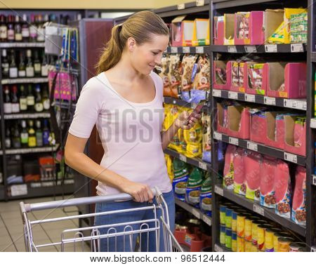 Pretty woman picking product in shelf in supermarket