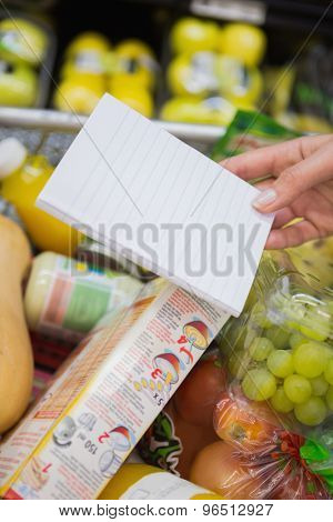 Woman writing in her notepad in aisle at supermarket