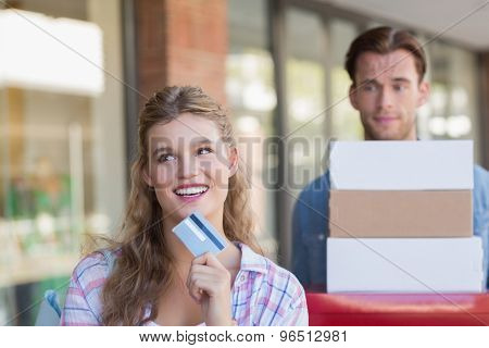 A happy couple showing their new credit card at the mall
