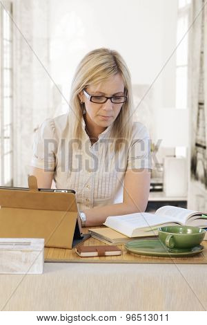 Blonde woman sitting at desk, reading book, using tablet computer.