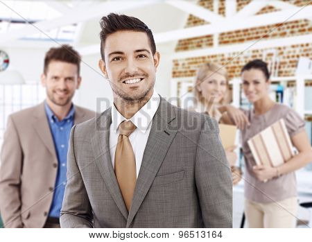 Portrait of successful young businessman, smiling, looking at camera.
