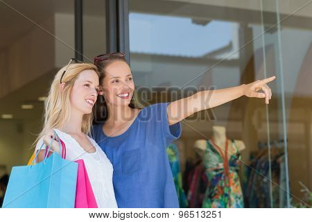 Smiling hipster girls friends finger pointing
