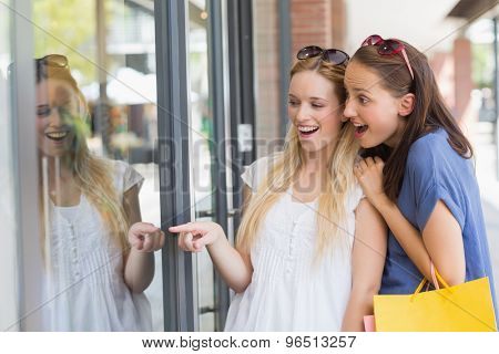 Shocked friends finger pointing through the window shop