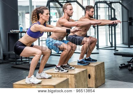 Three muscular athletes doing jumping squats on a wooden box