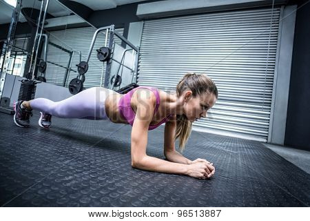 Side view of a muscular woman on a plank position