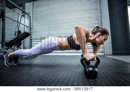 Side view of a woman doing pushups with kettlebells
