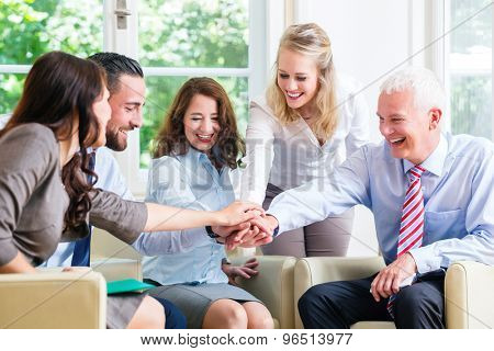 Team of business people celebrating success stacking hands together