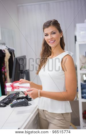 Portrait of smiling woman redeeming a gift card and looking at camera at a boutique