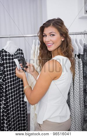 Portrait of smiling woman taking a photo of price tag at a boutique