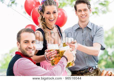 Three friends in Munich Beer garden clinking