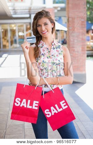 Portrait of smiling woman with sale shopping bags showing credit card at the shopping mall