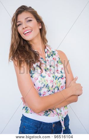 Portrait of smiling young woman with arms crossed against a white background