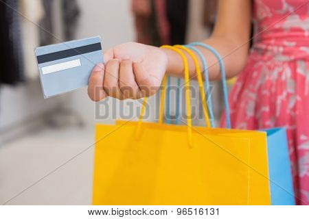 Woman with shopping bags paying by credit card at a boutique