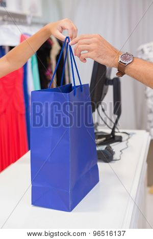 Cashier giving customer a blue shopping bag at a boutique