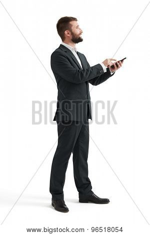 sideview photo of smiley businessman in formal wear using smartphone and looking up. isolated on white background