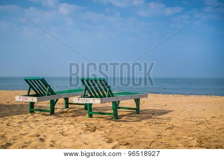 Two deck chairs on empty sandy beach.
