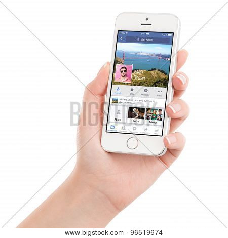 Female Hand Holding White Apple Iphone 5S With Facebook App On The Display
