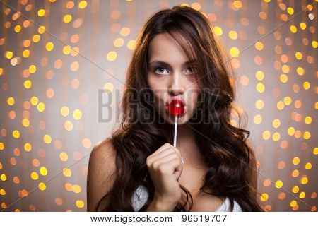 Pretty long-haired brunette with lollipop looking at camera on sparkling background