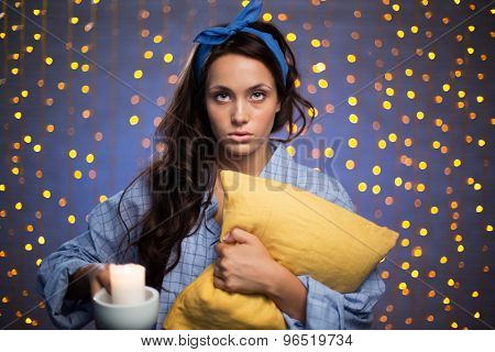 Young woman with burning candle and pillow looking at camera on sparkling background