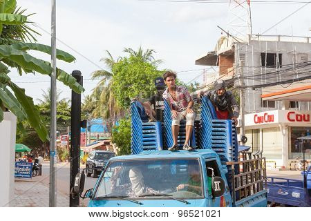 Guys ride in the back of the truck on blue plastic chairs