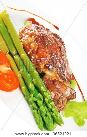 steak of beef meat served on white plate with asparagus isolated over white background . shallow dof
