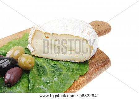 camembert cheese on wooden platter with olives and tomato isolated over white background