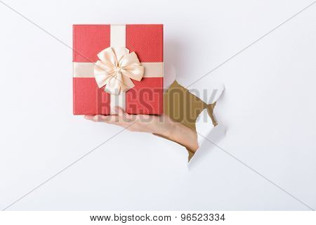 Hand break through paper with red present box