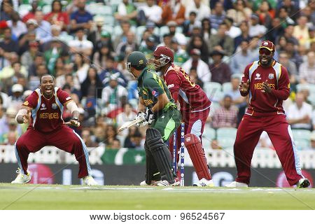 LONDON, ENGLAND - June 07 2013: Pakistan's Kamran Akmal is dismissed by Denesh Ramdin during the ICC Champions Trophy cricket match between Pakistan and The West Indies at The Oval Cricket Ground.