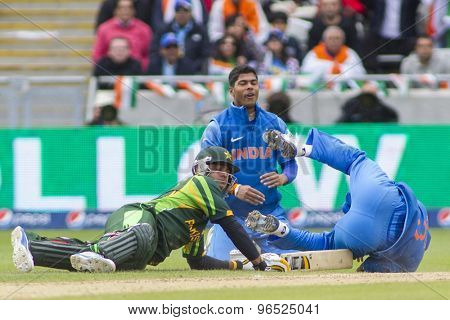 EDGBASTON, ENGLAND - June 15 2013: Pakistan's Mohammad Hafeez and India's Mahendra Singh Dhoni  during the ICC Champions Trophy cricket match between India and Pakistan at Edgbaston Cricket Ground.