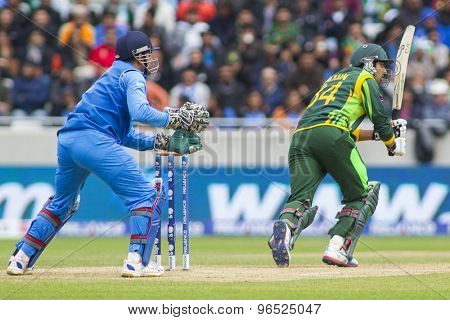 EDGBASTON, ENGLAND - June 15 2013: India's Mahendra Singh Dhoni and Pakistan's Umar Amin during the ICC Champions Trophy cricket match between India and Pakistan at Edgbaston Cricket Ground.