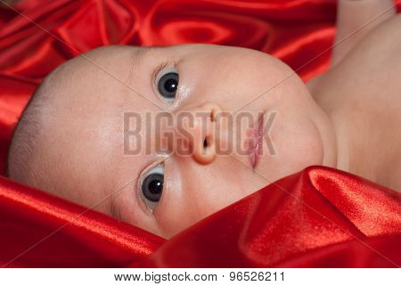 Newborn Baby Is Lying On Red Silk Looking Upwards Surprisingly