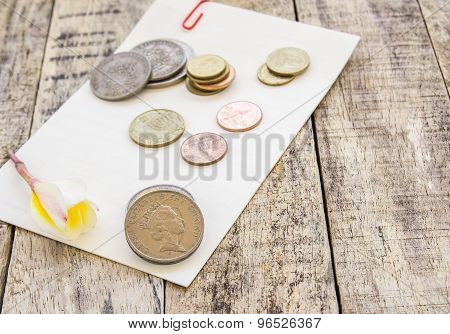 Coin And Flower On White Paper On Wooden Table
