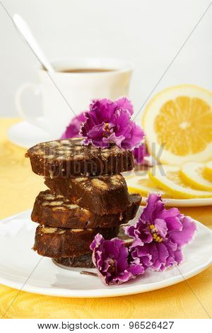 Pile Of Delicious Chocolate Cake Slices With The Cookies Filling, Decorated Violet Flowers On A Whit