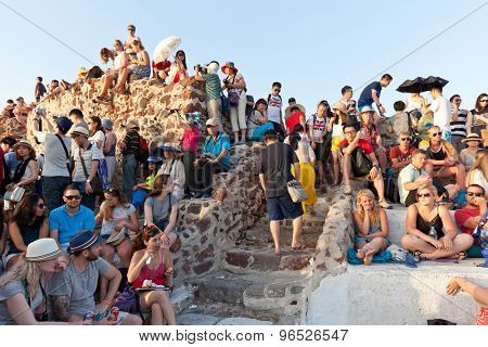 Oia,Santorini, GREECE - June 14, 2015:A CROWD OF TOURISTS AWAITS THE FAMOUS SANTORINI SUNSET