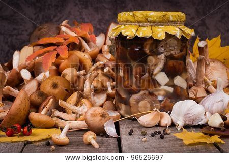 A Lot Of Fresh And Preserving  In Glass Jar Mushrooms With Spices On Wooden Table