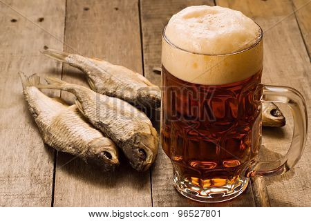 Pint Of Beer And Dried Fish On Wooden Table