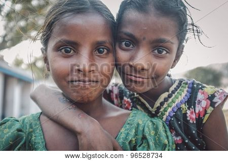 HAMPI, INDIA - 31 JANUARY 2015: Two Indian girls hug and smile. Post-processed with grain, texture and colour effect.