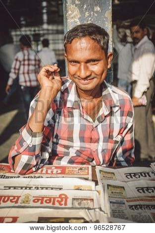 MUMBAI, INDIA - 08 JANUARY 2015: India man sells newspapers in front of train station. Post-processed with grain, texture and colour effect.