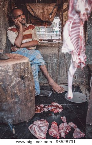 MUMBAI, INDIA - 12 JANUARY 2015: Indian butcher speaks on cellphone at work in Dharavi slum. Post-processed with grain, texture and colour effect.