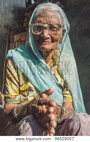 GODWAR REGION, INDIA - 13 FEBRUARY 2015: Elderly Indian woman in sari with covered head and repaired glasses sits in doorway of home. Post-processed with grain, texture and colour effect.